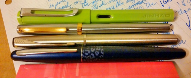 Here we have a Pilot Metropolitan at the bottom leaning on a little Clairfontaine notepad, with a Parker Latitude above it, a Duke 209 above that, and a Jinhao 599 above that. And words on a sheet of paper beneath them all.